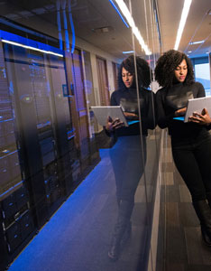 woman holding laptop near servers